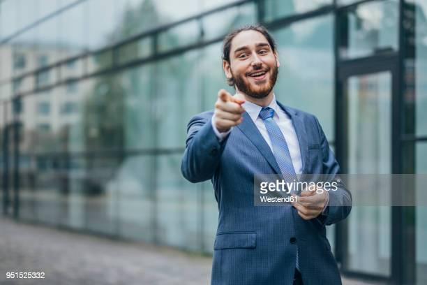 portrait of happy businessman standing outdoors pointing his finger - gestikulieren stock-fotos und bilder