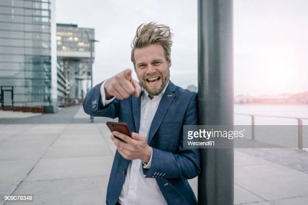 Portrait of happy businessman with cell phone in the city