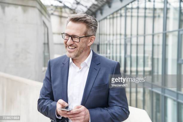 portrait of happy businessman with cell phone - solo un uomo maturo foto e immagini stock