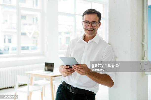 portrait of happy businessman with tablet in bright office - leaning stock pictures, royalty-free photos & images