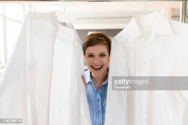 portrait of happy businesswoman between two white shirts - bluse stock-fotos und bilder