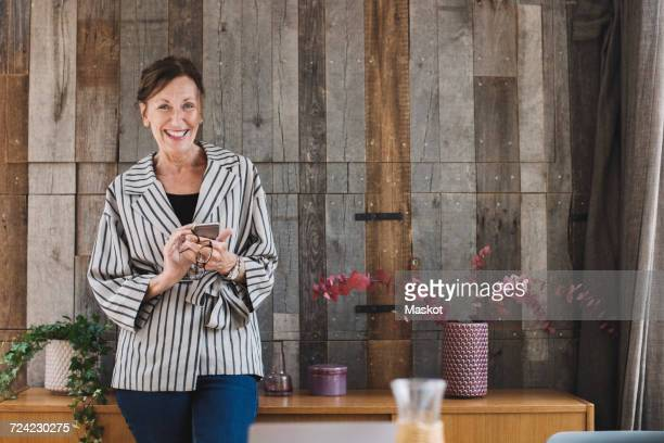 Portrait of happy businesswoman holding smart phone against wood paneling in portable office truck