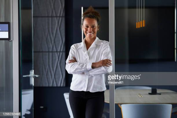 portrait of happy businesswoman leaning at door case of board room in modern office - founder stock pictures, royalty-free photos & images