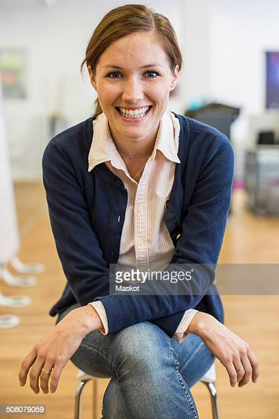 Portrait of happy businesswoman sitting on chair in office