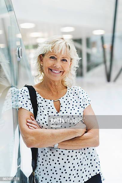 Portrait of happy businesswoman standing arms crossed in modern office