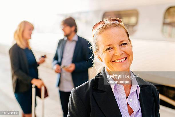 Portrait of happy businesswoman standing at railroad station with colleagues discussing in background