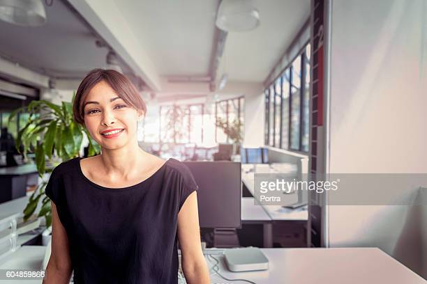 Portrait of happy businesswoman standing in office