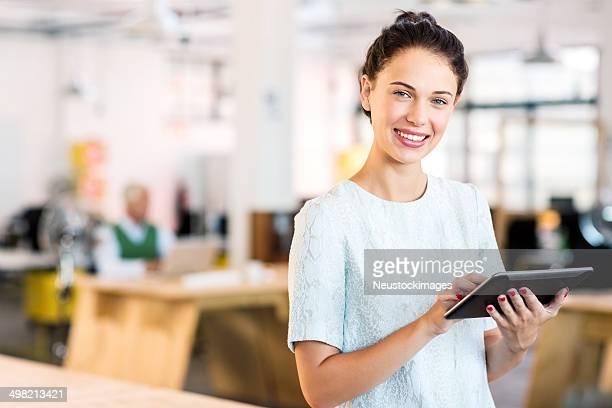Portrait Of Happy Businesswoman Using Digital Tablet