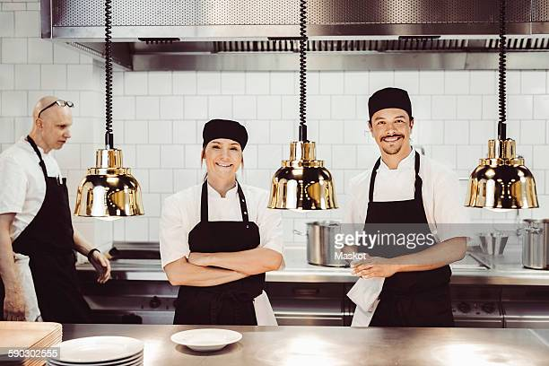 Portrait of happy chefs standing at commercial kitchen counter