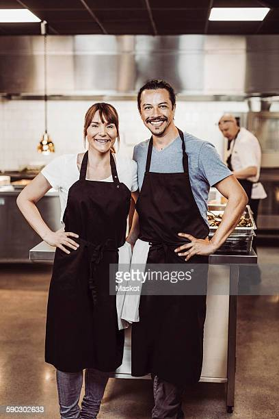 Portrait of happy chefs standing in commercial kitchen
