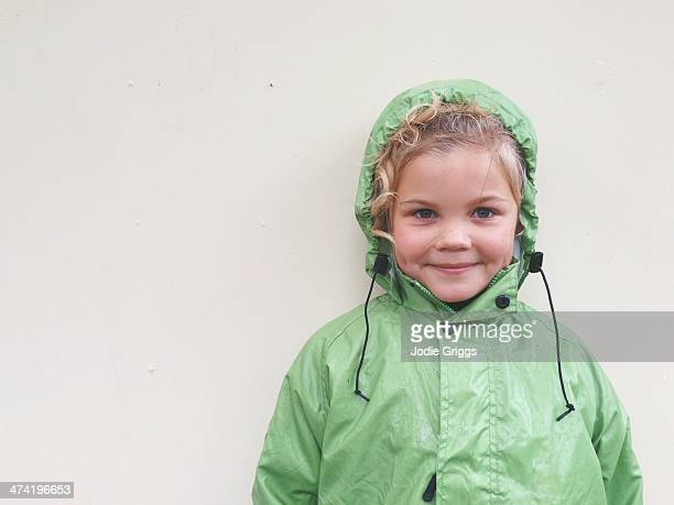 Portrait of happy child wearing green rain coat
