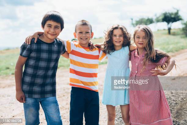 portrait of happy children friendship - arm in arm stock pictures, royalty-free photos & images