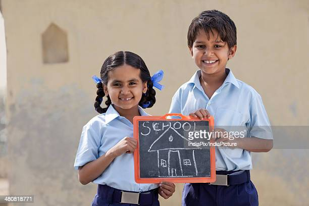 Portrait of happy children holding slate with school drawn on it