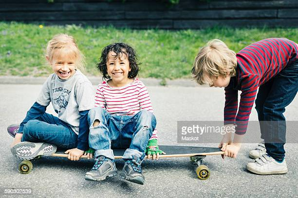 Portrait of happy children sitting on skateboard while friend pulling it at yard