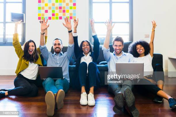 Portrait of happy colleagues cheering sitting on floor with laptops