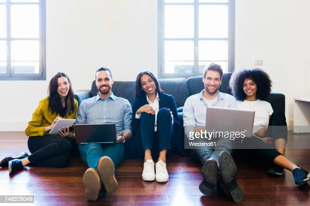 Portrait of happy colleagues sitting on couch with laptops