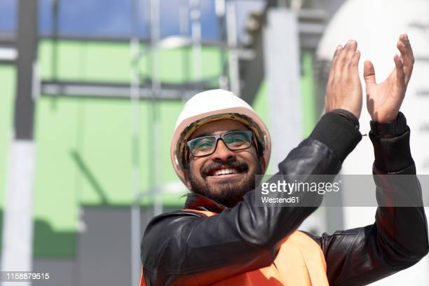portrait of happy construction engineer in front of power station wearing hard hat and safety vest clapping hands - taper dans les mains photos et images de collection