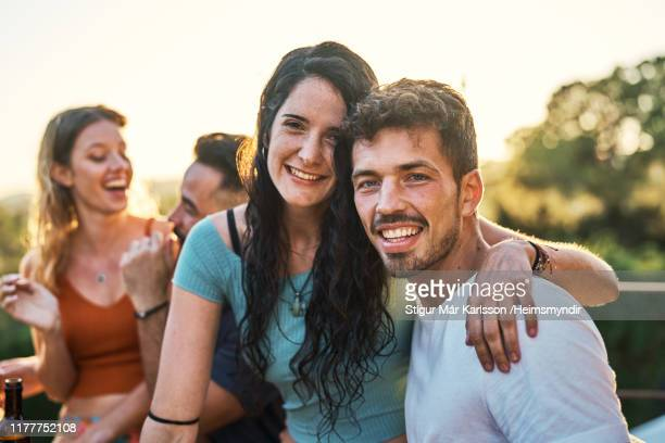 portrait of happy couple at balcony during reunion - stubble stock pictures, royalty-free photos & images