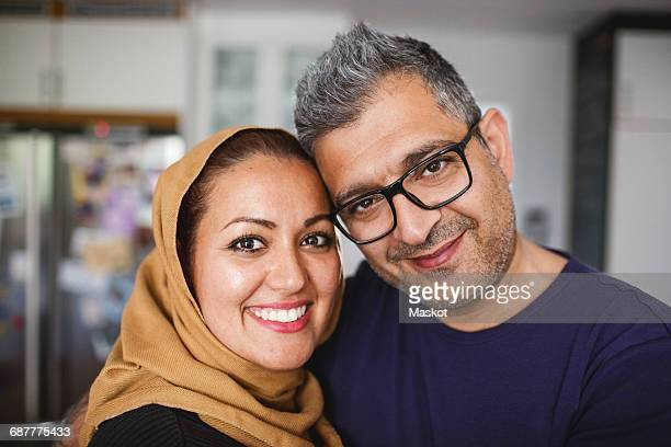 portrait of happy couple at home - muslim couple stock pictures, royalty-free photos & images
