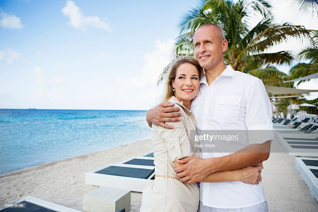 Portrait of happy couple embracing on beach : ストックフォト