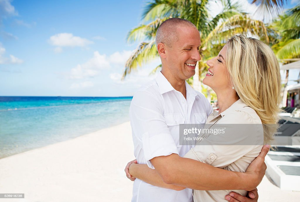 Portrait of happy couple embracing on beach : Bildbanksbilder