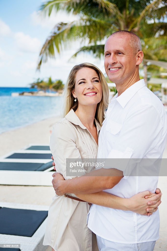 Portrait of happy couple embracing on beach : Photo