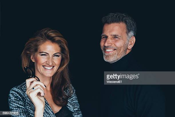 Portrait of happy couple in front of black background