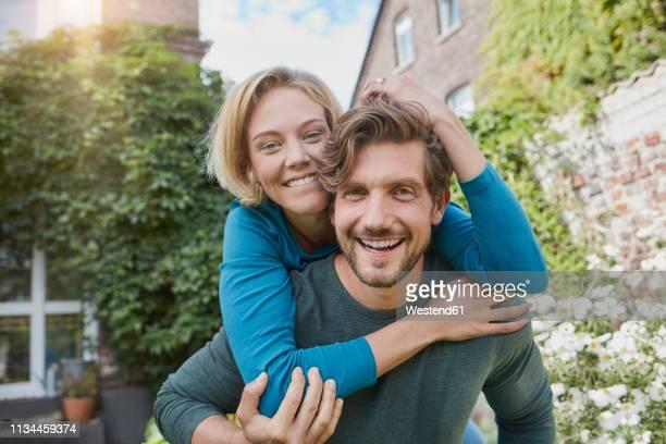 portrait of happy couple in garden of their home - 30 34 jahre stock-fotos und bilder