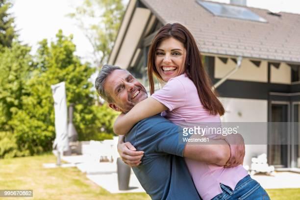 portrait of happy couple in garden of their home - frauen über 30 stock-fotos und bilder