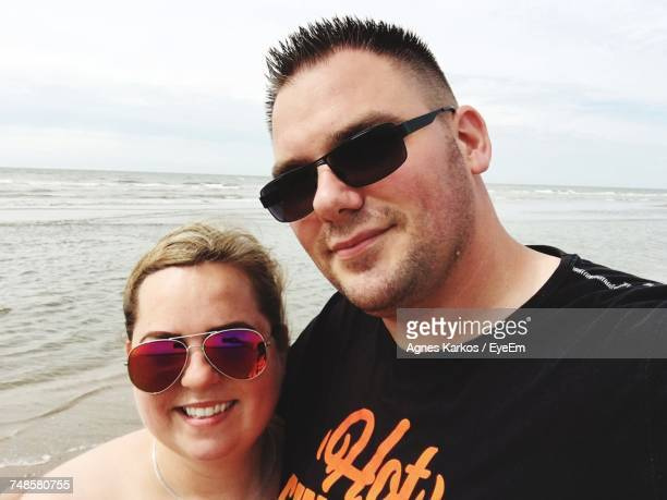 Portrait Of Happy Couple In Sunglasses Standing At Beach Against Cloudy Sky