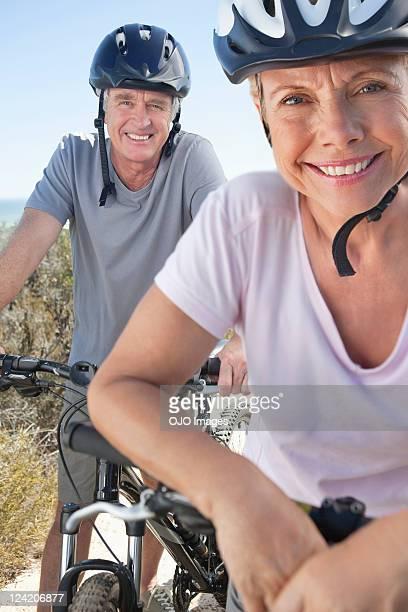 Portrait of happy couple mountain biking in cycling helmet