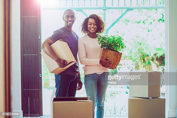 Portrait of happy couple moving house