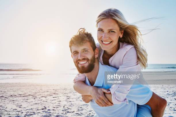 portrait of happy couple on the beach - heteroseksueel koppel stockfoto's en -beelden