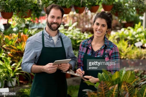 Portrait des propriétaires heureux couple d'une jardinerie en regardant la caméra en souriant