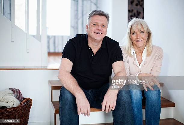 Portrait of happy couple sitting on steps