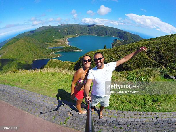 Portrait Of Happy Couple Taking Selfie While Standing On Retaining Wall Against Lagoa Do Fogo