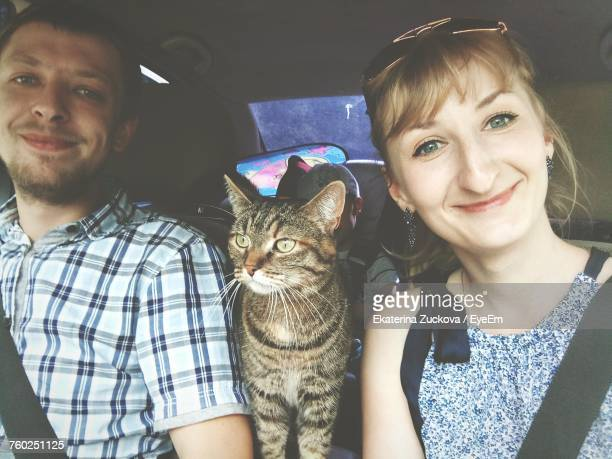 Portrait Of Happy Couple With Cat Traveling In Car
