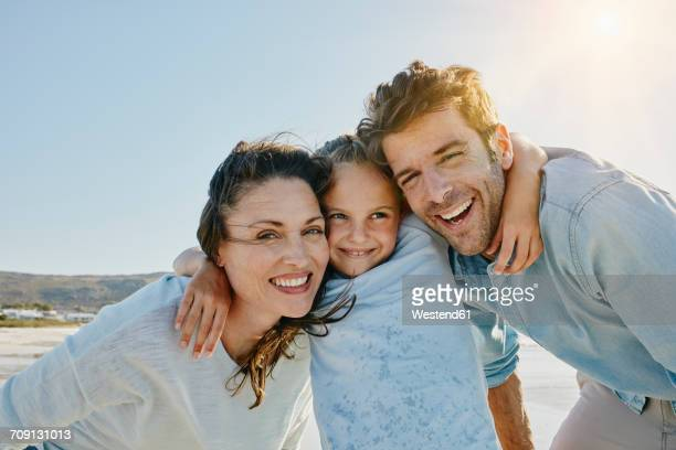 Portrait of happy couple with daughter on the beach
