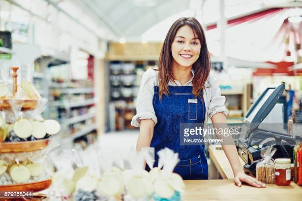 portrait of happy deli owner leaning on checkout counter - convenience store counter stock photos and pictures