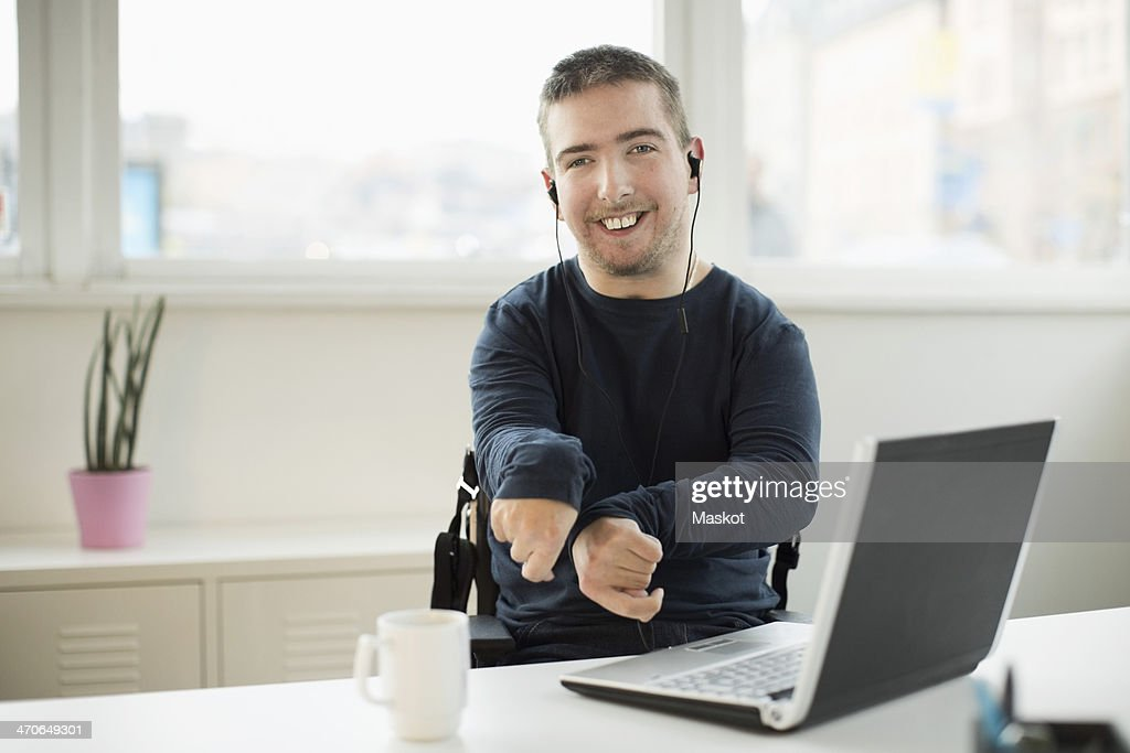 Portrait of happy disabled businessman with laptop at desk in office : Stock Photo