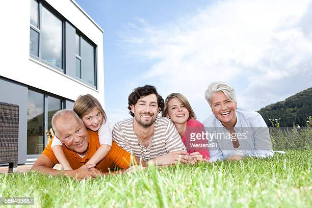 Portrait of happy extended family lying on lawn