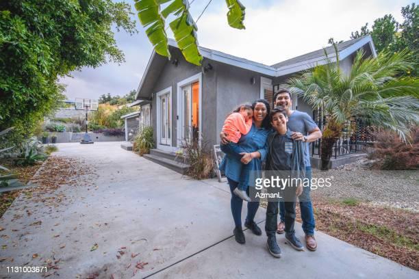 portrait of happy family against house - california meridionale foto e immagini stock