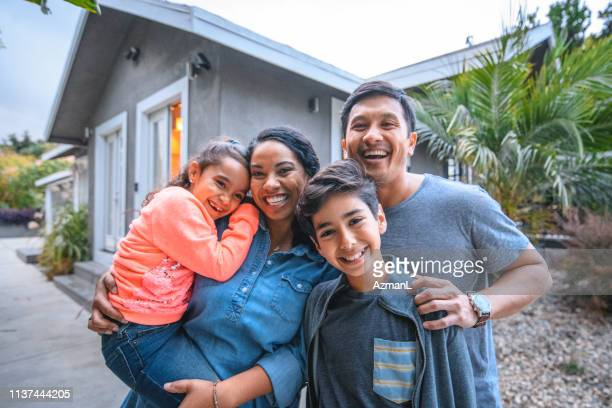 portrait of happy family against house - familia imagens e fotografias de stock