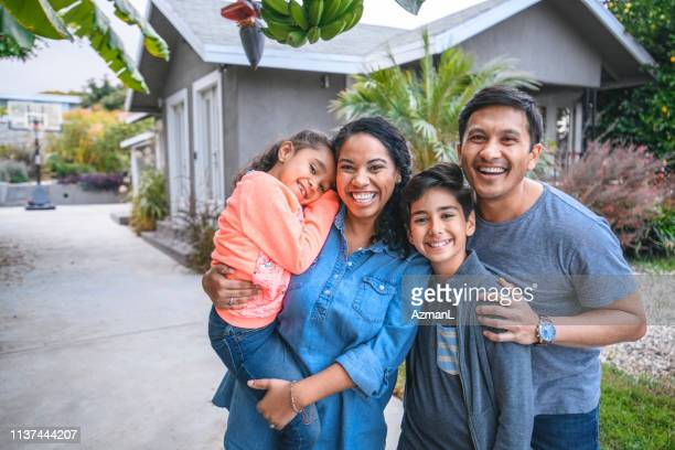 portrait of happy family against house - latin american and hispanic ethnicity stock pictures, royalty-free photos & images