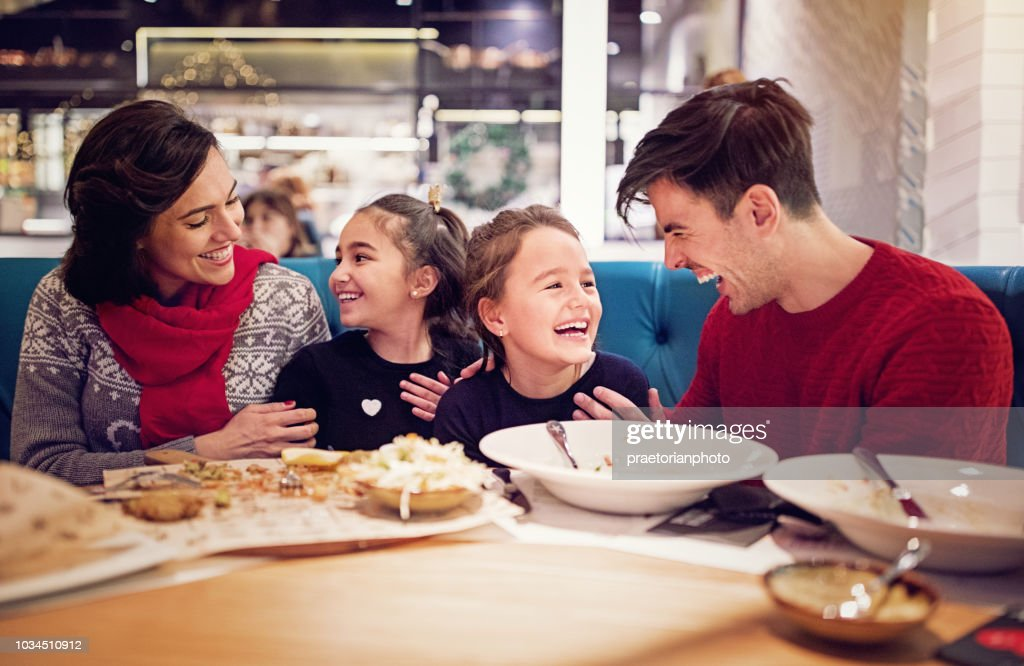 Portrait of happy family eating in the restaurant at Christmas : Stock Photo