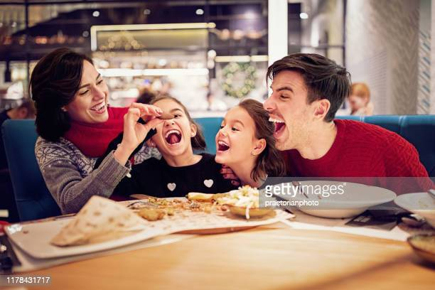 portrait of happy family eating in the restaurant at christmas - restaurant stock pictures, royalty-free photos & images