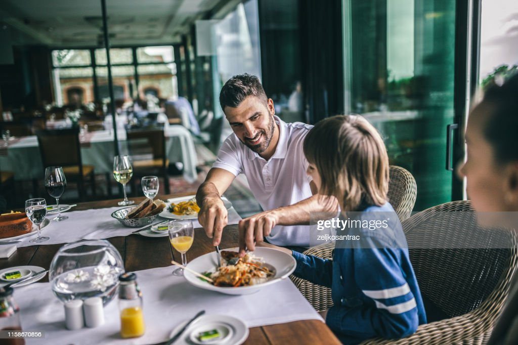 Portrait of happy family eating in the restaurant : Stock Photo