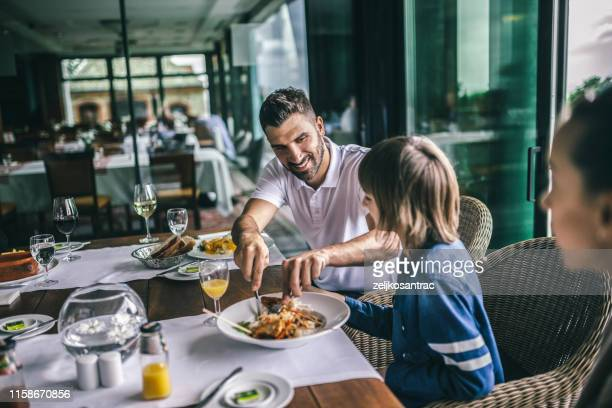 portrait of happy family eating in the restaurant - restaurant stock pictures, royalty-free photos & images