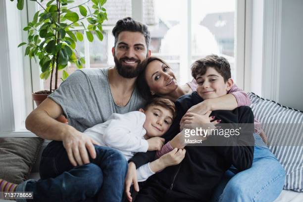 Portrait of happy family enjoying on sofa in living room at home