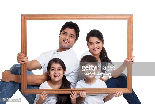 Portrait Of Happy Family Holding Frame Stock Photo | Getty Images